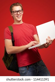 portrait of young man holding laptop and wearing backpack over red background