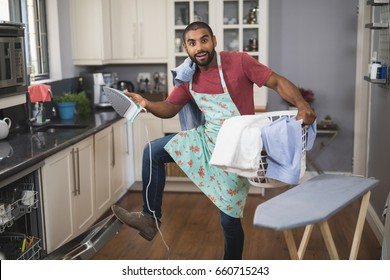 Portrait of young man holding laundry basket and iron while closing dishwasher in kitchen at home