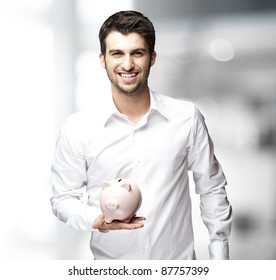 Portrait of young man holding a piggy bank indoor