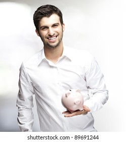 portrait of young man holding piggy bank indoor