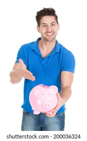 Portrait of young man holding piggybank isolated over white background