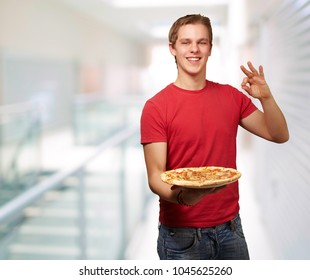 portrait of young man holding pizza and doing good gesture at modern building