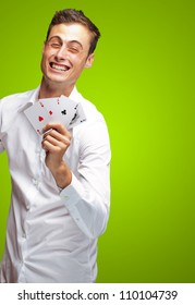 Portrait Of Young Man Holding Poker Cards Isolated On Green Background