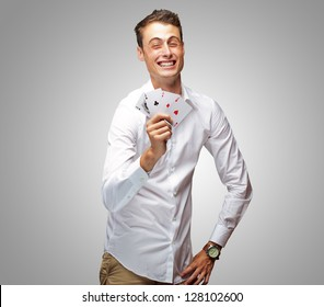 Portrait Of Young Man Holding Poker Cards Isolated On Grey Background