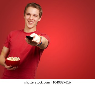portrait of a young man holding popcorn on red background