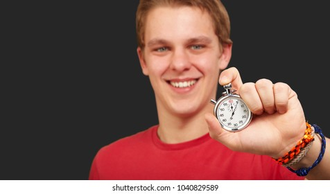 Portrait of a young man holding a stopwatch on black background