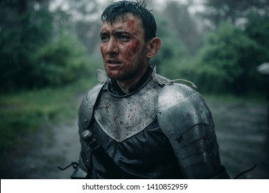 Portrait of young man in the image of a medieval knight in armor with blood and wounds on his face in the rain.