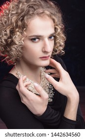 portrait of a young man in the image of a woman with makeup and hair. Androgyn model.