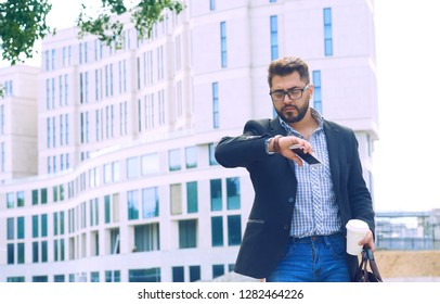 Portrait of a young man in a jacket with a beard and glasses walking down the street drinking coffee and looking at the clock.