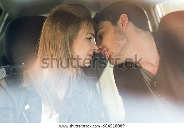 portrait of young man kissing beautiful girlfriend while sitting in car