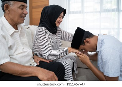 portrait of young man kneeling and kiss his parent's hand asking for forgivness. indonesian traditional gesture sungkem. eid mubarak or ramadhan