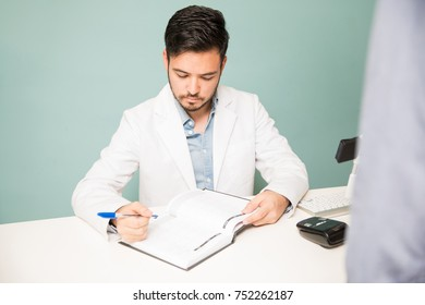 Portrait of a young man in a lab coat making an appointment for a customer in a front desk at a spa