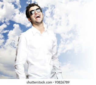 portrait of a young man laughing against a sky background