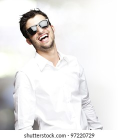 portrait of a young man laughing with sunglasses, indoor