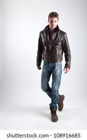 Portrait of young man with leather jacket against white background.