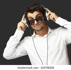 portrait of a young man listening to music using headphones over a black background