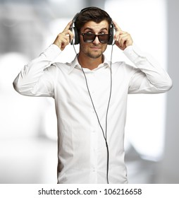portrait of a young man listening to music using headphones indoor