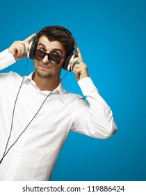 portrait of young man listening to music using headphones over blue
