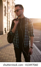 Portrait of young man listening to music with mobile phone in the street.