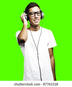 portrait of young man listening to music against a removable chroma key background