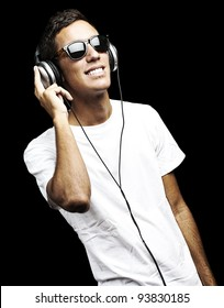 portrait of a young man listening to music with headphones against a black background
