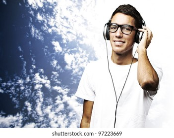 portrait of a young man listening to music against a blue sky background