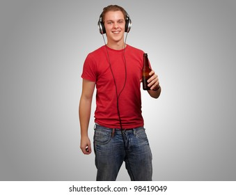 portrait of a young man listening to music while holding a beer against a grey background