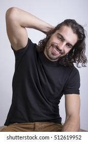 Portrait of young man with long hair and white background