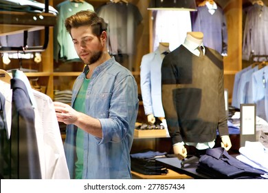 Portrait of a young man looking at clothes to buy at shop
