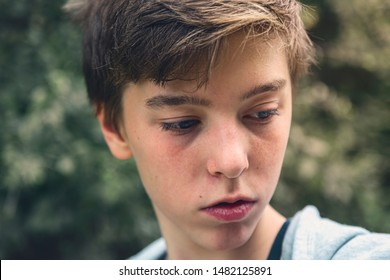 Portrait of a young man looking down, lost in thought