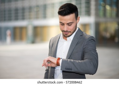Portrait of a young man looking at his wrist watch