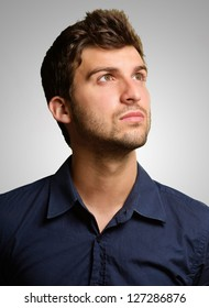 Portrait Of Young Man Looking Up On Grey Background