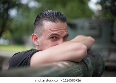 portrait of young man looking over his arms while leaning on pipe