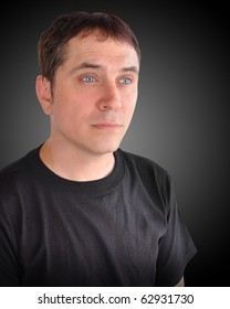 A portrait of a young man looking to the side. The model wearing a black t-shirt for a casual look and there is a black background.