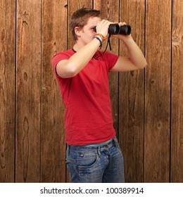 portrait of a young man looking through binoculars against a wooden wall