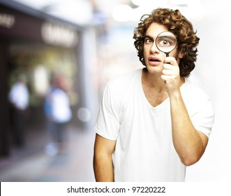 portrait of a young man looking through a magnifying glass at a crowded place