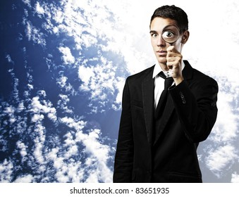 portrait of a young man with a magnifying glass against a blue sky background