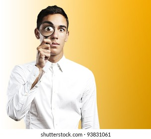 portrait of a young man with a magnifying glass on a yellow background