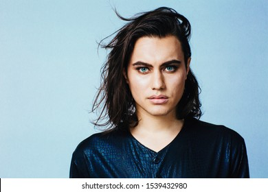 Portrait of a young man with make up and long hair in studio