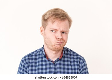Portrait of young man making excuses for having perplexed. Human face expressions, emotions, mistrust and feelings concept on white background