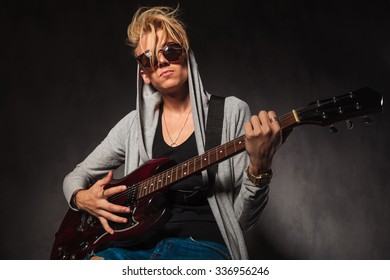 portrait of young man with messy hair playing electric guitar in studio while wearing sunglasses