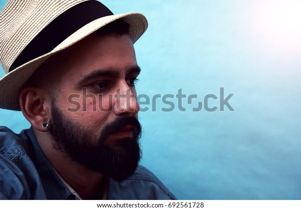 Portrait of young man model with a hat and blue background with flash of light