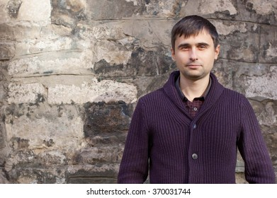 Portrait of a young man near the old wall, he looks toward