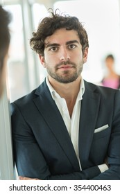 Portrait of a young man with in nice business suit leaning against a glass door in a luminous open space. He has a beard, dark hair and his arms crossed, he is smiling and looking at camera