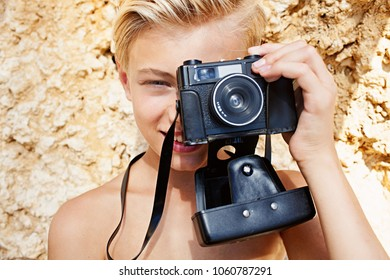 Portrait of young man on beach rock texture using traditional film old photographic camera to take pictures, summer sunny beach, nature outdoors. Teenager photo hobby, holiday leisure travel lifestyle