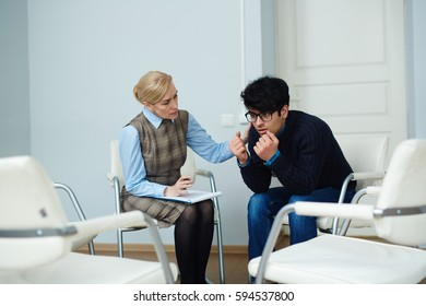 Portrait of young man opening up his problems to mental health doctor comforting him after support group meeting