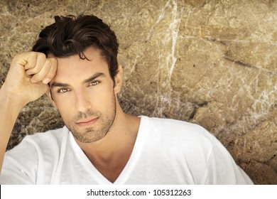 Portrait of young man outdoors with very handsome face in white casual shirt against natural background