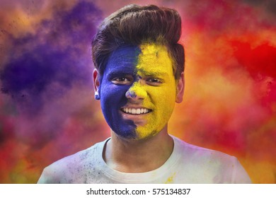 Portrait Of Young Man With Paint On Face During Holi