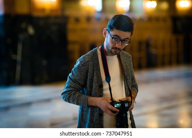 Portrait of a young man photographer with glasses looking at the camera, in big hall