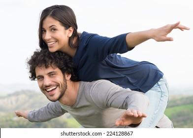 Portrait Of Young Man Piggybacking His Girlfriend Outdoor